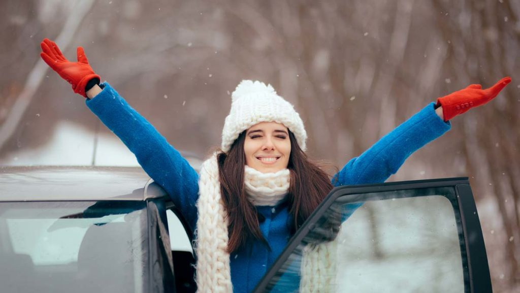Woman celebrates after buying a car in winter