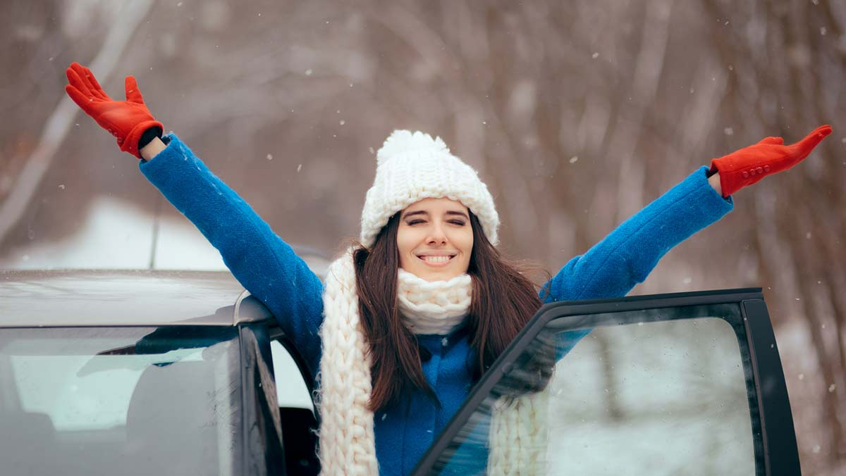 Woman dressed for winter with armed raised looking happy with car