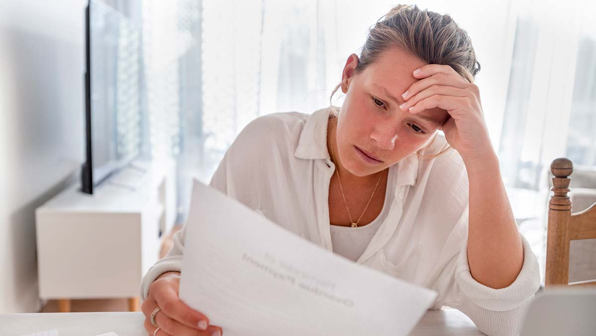 Woman concentrates while reviewing documents to understand her car insurance deductible