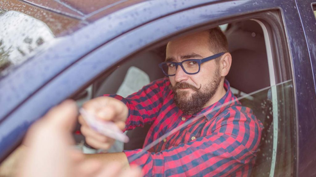 Man hands license to police officer - do speeding tickets affect car insurance