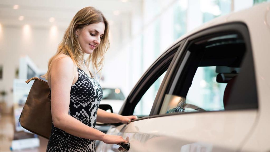 Woman is in a dealership buying a new car - opening a floor model car door.