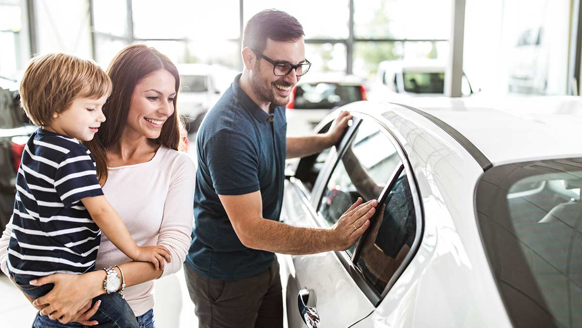 Happy couple with child buying a used car - shopping in a dealership