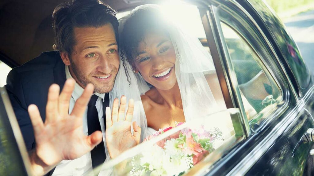 Car Insurance For Married Couples - Couple in car waving on goodbye on wedding day