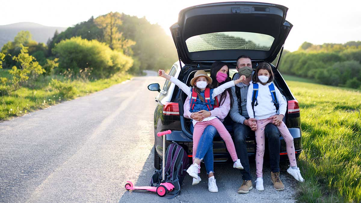 Family in car wearing masks going on a post-pandemic road trip.